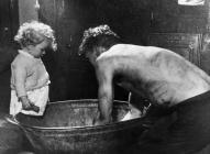 17. Miner washing at home in tin bath