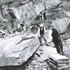 Quarrymen splitting a large block of slate in...