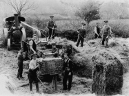 Soldiers at work bailing hay.