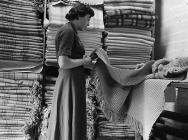 A woman checking woollen blankets, Dinas...