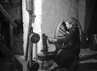 A worker at a spinning wheel, Penmachno Woollen...