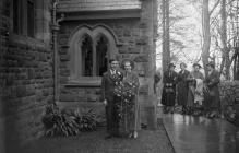 Photograph of a bridal couple outside a church,...