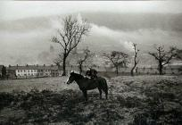 A child rides a horse with the village of...