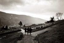 Three mothers walk back to the village of...