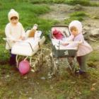 Two girls playing with prams