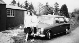 Two women in front of car