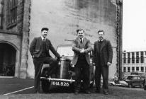 Three men in front of car