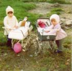 Two young girls playing with toy prams