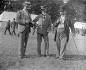 Three gentlemen pose at an agricultural show in...