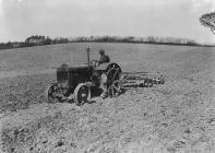 Man harrowing with tractor and disk harrow