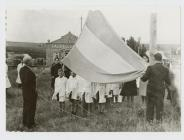 Children wearing white coats standing under the...
