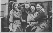 Marge Evans with 4 co-workers inside the factory.