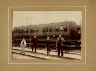Railway workers, standing by passenger coach.