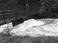 River Dulas in flood under footbridge